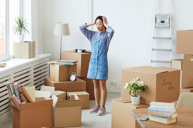Pełnowymiarowy portret sfrustrowanej azjatyckiej kobiety panikującej, stojącej wśród kartonowych pudeł w pustym pokoju, koncepcji przeprowadzki lub relokacji