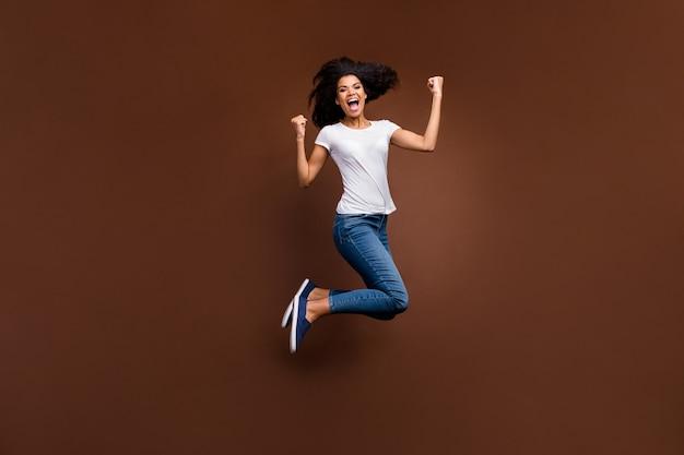 Pełnowymiarowy portret śmiesznej, dzikiej ciemnej skóry pani skaczącej z niesamowitymi emocjami uczęszczającymi na mecz piłki nożnej nosić casualową białą koszulkę jeansową.