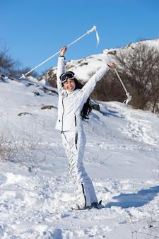 Pełnowymiarowy portret szczęśliwej kobiety o długich ciemnych włosach stojącej na nartach i trzymającej kijki nad głową na pokrytej śniegiem górze w dzień w jasnym słońcu, wyglądająca uroczyście i wolna