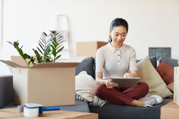 Pełnowymiarowy portret współczesnej azjatki używającej cyfrowego tabletu podczas rozpakowywania pudeł w nowym domu lub mieszkaniu