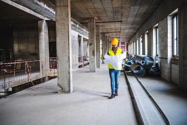 Pełnowymiarowy pracownik budowlany w odzieży roboczej chodzący w budynku w trakcie budowy i przeglądający plany. a