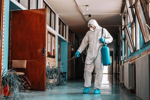 Pełnowymiarowy pracownik w sterylnym mundurze, z maską na twarz z rozpylaczem ze środkiem dezynfekującym i natryskowym korytarzem szkolnym.