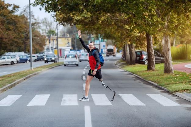 Pełnowymiarowy przystojny, niepełnosprawny sportowiec rasy kaukaskiej w stroju sportowym, ze sztuczną nogą i plecakiem, który przechodzi przez ulicę i macha do przyjaciela.