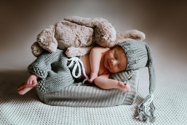 Pełnowymiarowy uroczy noworodek ubrany w dzianinowe spodnie i czapeczkę na głowie