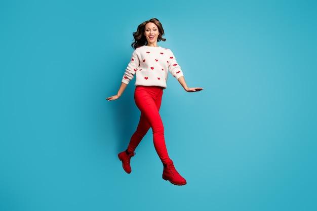 Pełnowymiarowy widok ładnej atrakcyjnej uroczej całkiem wesołej dziewczyny skaczącej na spacer, mającej na sobie odświętne ubrania