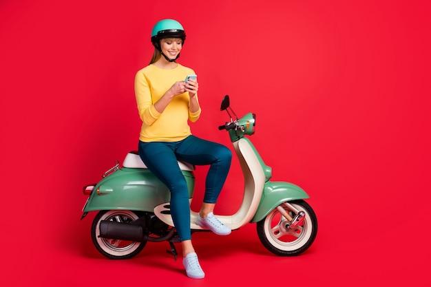 Pełnowymiarowy widok na wesołą dziewczynę siedzącą na motorowerze trzymaj sms-y na smartfonie