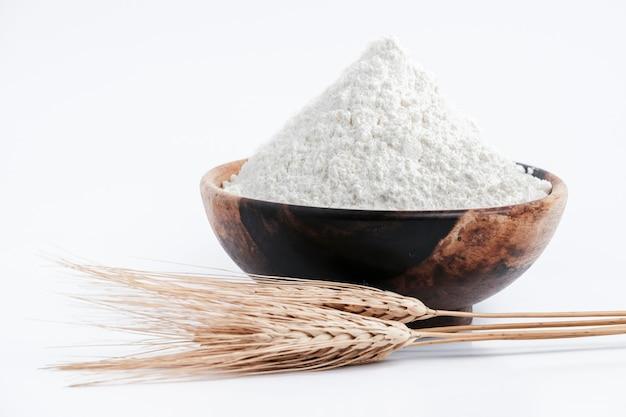 Pełnoziarnista mąka pszenna na białym tle. mąka pszenna wypełniona drewnianą miską