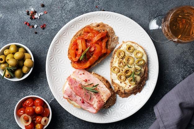 Pełnoziarniste kanapki z serem, bekonem i oliwkami w puszkach papryką z pomidorem na talerzu.