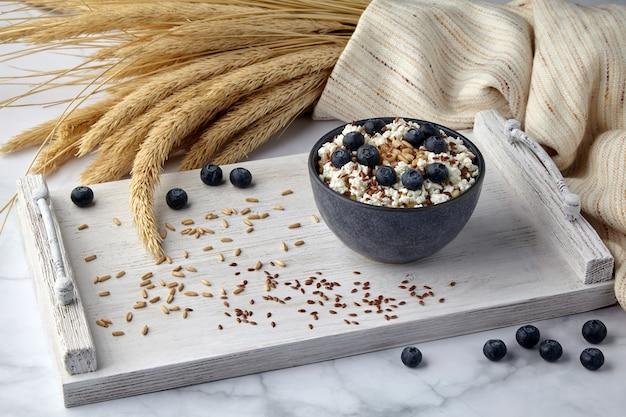 Pełnoziarniste płatki owsiane z twarogiem jagodowym i nasionami lnu oraz kłosami pszenicy na pomalowanej na biało drewnianej tacy. zdrowe odżywianie