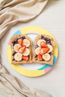 Pełnoziarnisty chleb tostowy ze świeżym bananem, truskawką i czekoladą na śniadanie