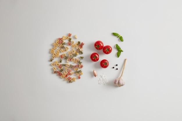 Pełnoziarnisty kolorowy makaron w kształcie litery na białym tle z pomidorami, solą morską, czosnkiem, ziarnami pieprzu, bogaty w kraby. zdrowe dodatki do makaronu, takie jak warzywa, tłuszcze, białko