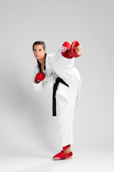 Pełny ciało kobieta z pudełkowatymi rękawiczkami na białym tle