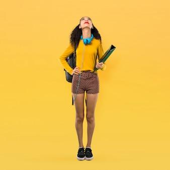 Pełny ciało nastolatka ucznia dziewczyna z kędzierzawego włosy stojakiem i patrzeć up na żółtym tle