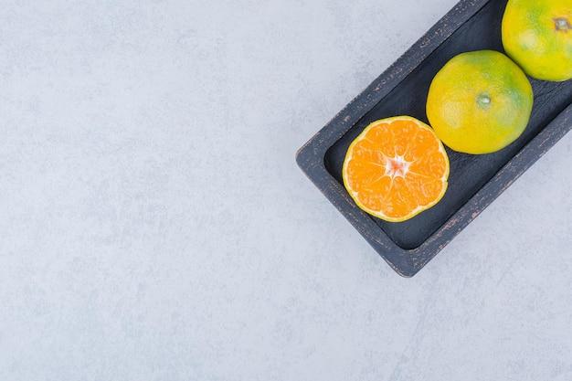 Pełny ciemny talerz kwaśnych mandarynek na białym tle. zdjęcie wysokiej jakości