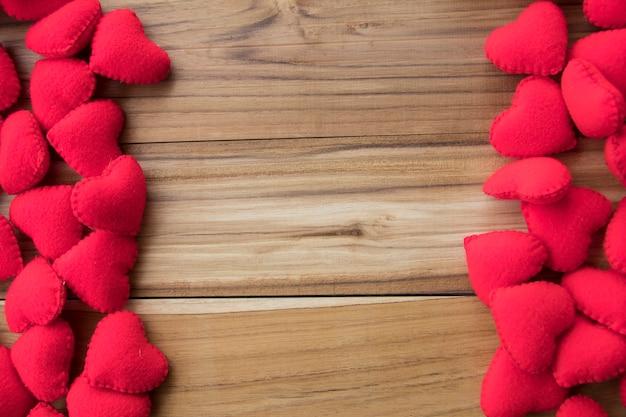 Pełny czerwony serca tło z kopii przestrzenią na drewnianym tle