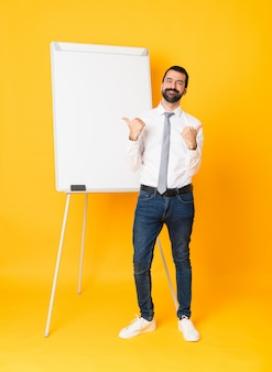 Pełny długość biznesmen daje prezentaci na białej desce nad odosobnioną kolor żółty ścianą z aprobatami ono uśmiecha się i gestem