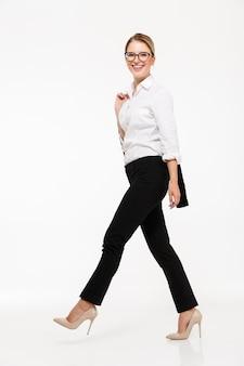 Pełny długość bocznego widoku wizerunek uśmiechniętej blondynki biznesowa kobieta chodzi w studiu i nad biel ścianą w eyeglasses
