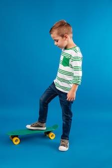 Pełny długość boczny widok pozuje z deskorolka młoda chłopiec