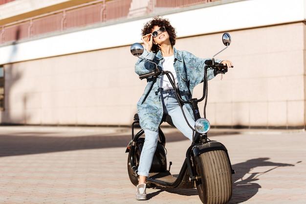 Pełny długość obrazek beztroska kędzierzawa kobieta siedzi na nowożytnym motocyklu outdoors i patrzeje daleko od w okularach przeciwsłonecznych