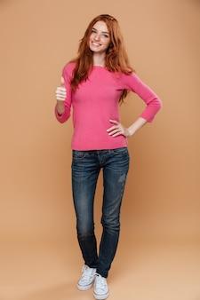 Pełny długość portret młoda uśmiechnięta rudzielec dziewczyna z aprobatami