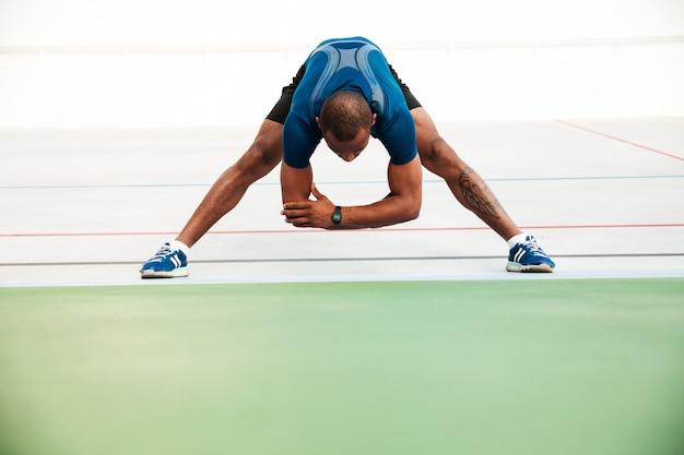Pełny długość portret młody sportowiec robi rozciąganiu
