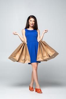 Pełny długość portret piękna młoda kobieta pozuje z torba na zakupy, odizolowywający