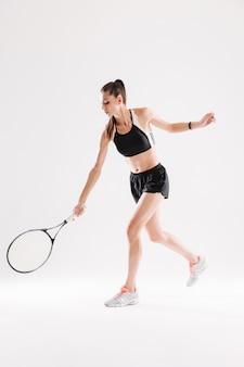 Pełny długość portret piękny kobiety gracz w tenisa