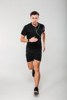 Pełny długość portret poważny młodego człowieka atleta