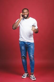 Pełny długość portret przystojny amerykanina afrykańskiego pochodzenia mężczyzna z telefonem komórkowym i zabiera filiżankę kawy. pojedynczo na czerwonym tle.