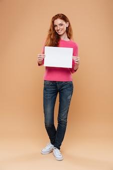 Pełny długość portret radosna ładna rudzielec dziewczyna trzyma pustego białego plakat