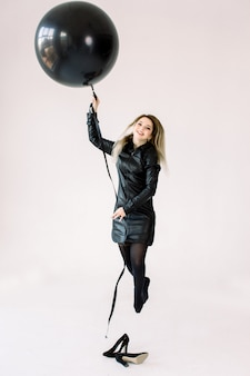 Pełny długość portret rozochocona młoda dziewczyna trzyma dużego czarnego lotniczego balon w czerni sukni podczas gdy skaczący i latający, patrzejący kamerę odizolowywającą nad białym tłem