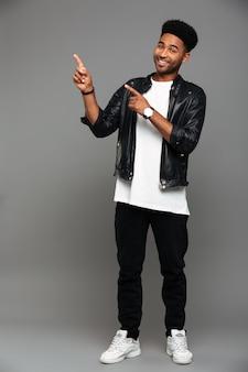 Pełny długość portret rozochocony przystojny afrykański mężczyzna wskazuje z dwoma palcami w stylowej odzieży, patrzeje