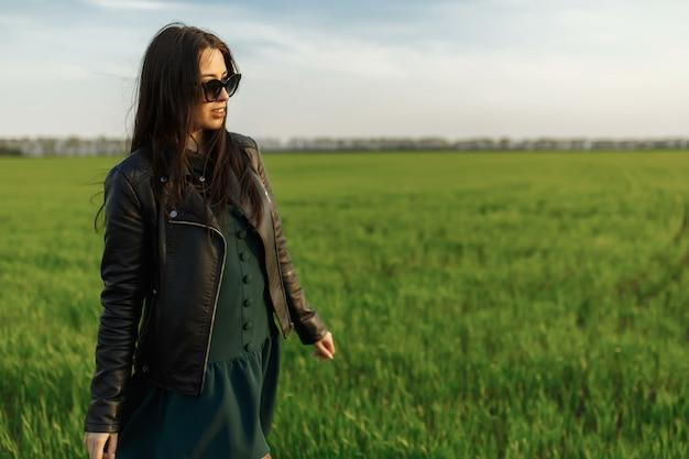 Pełny długość portret stylowa dziewczyna chodzi wzdłuż zielonego pola. młoda uśmiechnięta kobieta chodzi w naturze. zielona wiosna łąka