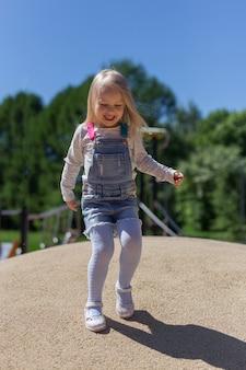 Pełny długość portret szczęśliwa blondynki 4 lat dziewczyna bawić się na boisku outdoors przeciw zielonym drzewom i niebieskiemu niebu