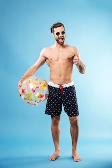 Pełny długość portret szczęśliwy facet trzyma plażową piłkę