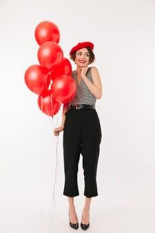 Pełny długość portret uśmiechnięta kobieta jest ubranym czerwonego beret