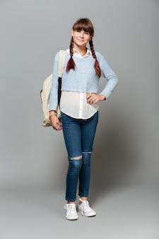 Pełny długość portret uśmiechnięta ładna uczennica z plecakiem