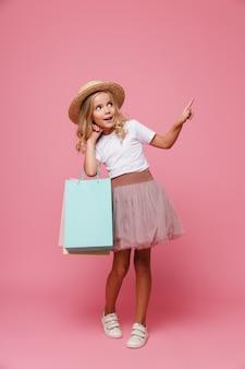 Pełny długość portret uśmiechnięta mała dziewczynka w kapeluszu