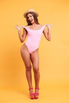 Pełny długość portret uśmiechnięta rozochocona dziewczyna jest ubranym swimsuit