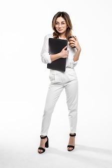 Pełny długość portret uśmiechnięty bizneswomanu przewożenia filiżanka kawy i laptop iść podczas gdy stać odizolowywam nad biel ścianą