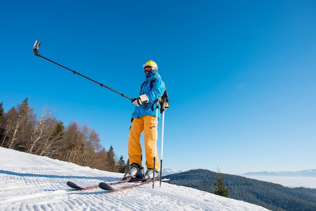 Pełny długość strzał narciarka stoi na górze góry w pogodnym zima dniu bierze selfie