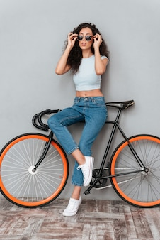 Pełny długość wizerunek dosyć kędzierzawa kobieta w okularach przeciwsłonecznych pozuje z bicyklem nad szarym tłem