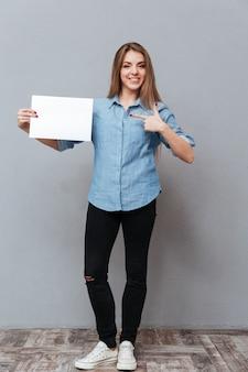 Pełny długość wizerunek kobieta w koszula pokazuje puste miejsce deskę