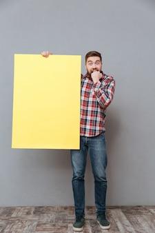 Pełny długość wizerunek przestraszony mężczyzna trzyma puste miejsce deskę