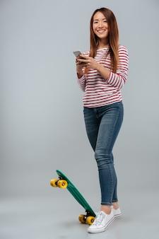 Pełny długość wizerunek szczęśliwa azjatykcia kobieta z deskorolka