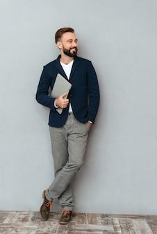 Pełny długość wizerunek szczęśliwy brodaty mężczyzna w biznesowym odzieżowym mienie laptopie i patrzeć awayy nad popielatym