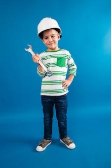 Pełny długość wizerunek uśmiechnięta młoda chłopiec w ochronnym hełmie