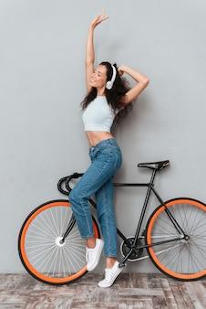 Pełny długość wizerunek zadowolona kędzierzawa kobiety pozycja z bicyklem i słuchająca muzyka hełmofonem z zamkniętymi oczami nad szarym tłem