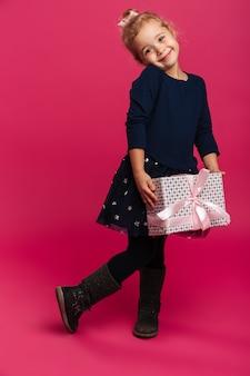 Pełny długość wizerunek zadowolona młoda dziewczyna trzyma prezenta pudełko