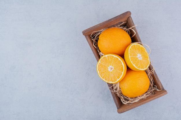 Pełny drewniany kosz słodkich pokrojonych pomarańczy. zdjęcie wysokiej jakości